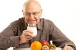 Senior man having a healthy breakfast isolated on white