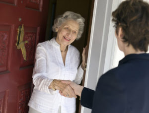 Smiling senior woman greeting visitor at the front door