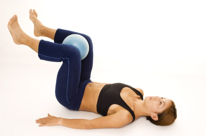 A female fitness instructor demonstrates an abductor squeeze - start